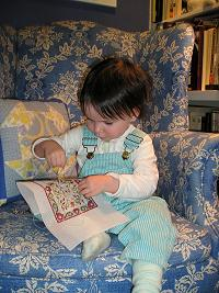 Very young girl stitching a dollhouse needlepoint carpet