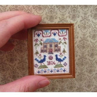 Dollhouse needlepoint sampler Peacock being held