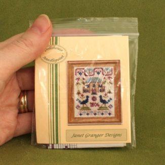 Dollhouse needlepoint sampler Peacock held for scale