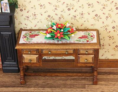 A needlepoint table runner on a dollhouse sideboard