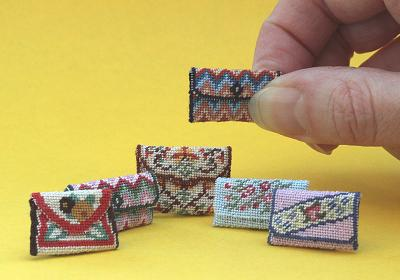 A collection of miniature needlepoint clutch bags for your dollshouse
