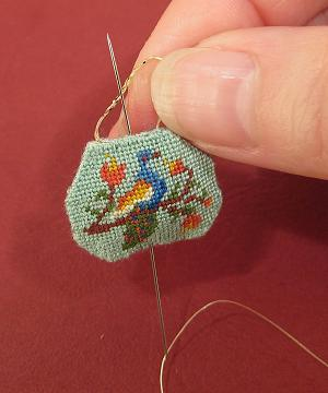 Miniature needlepoint tutorial - poke the needle up from the seam in the base of the bag and out of the centre top